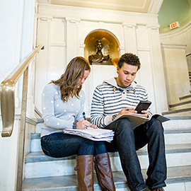 students sitting on the steps of Lincoln Hall lobby