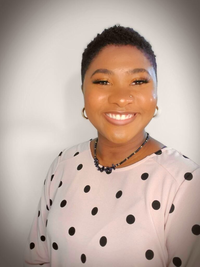 A Black woman wearing a pink shirt with black polka dots and smiling