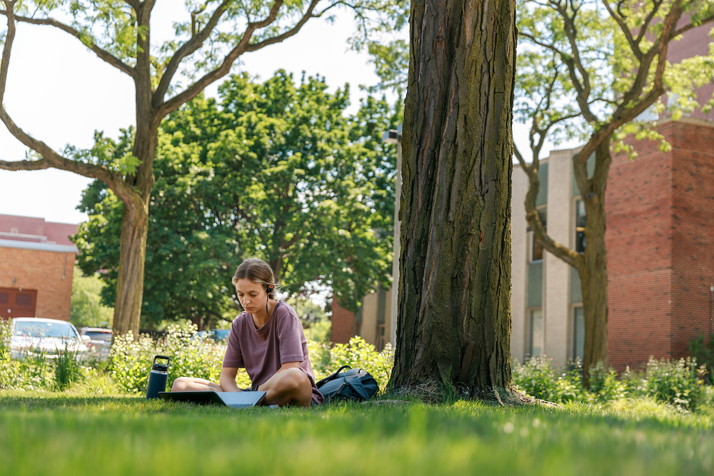 A student studying outside on quad of east campus