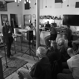 Jessie Shelton, professor of physics, speaks to a crowd at Pizza M in Urbana during the Astronomy on Tap event. (Photo courtesy of Joaquin Vieira.)