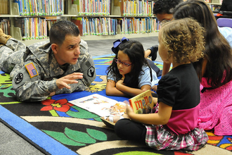 Man in military uniform laying on the floor talking to three children sitting in a circle around him. There are toys on the floor and it looks like he is teaching them something.