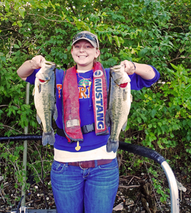 Figure 1.  Cassidy Miles, IRBS technician, holding two big largemouth bass collected from the Dresden pool of the upper Illinois River.