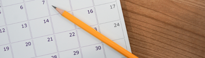 calendar laying on a desk with a pencil laying on top of the calendar