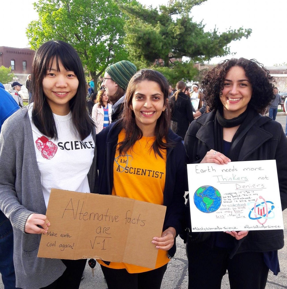3 female graduate students holding their signs at the Champaign-Urbana March for Science