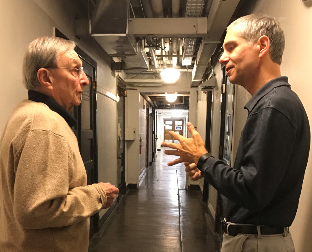 Richard Dehm and Martin Gruebele, talking in a hallway in Noyes Lab