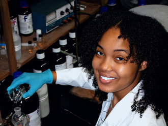 Photo of Enleyona Weir in the lab in a lab coat and blue gloves
