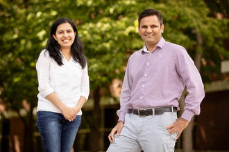 Graduate student Dinumol Devasia stands to the right of chemistry professor Prashant Jain with green leafy trees in the background.