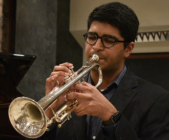 Portrait of Phil Kocheril playing a trumpet at a concert