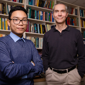 Image of Martin Gruebele, right, and graduate student Huy Nguyen, left, standing next to each other in front of a wall of bookshelves filled with books.
