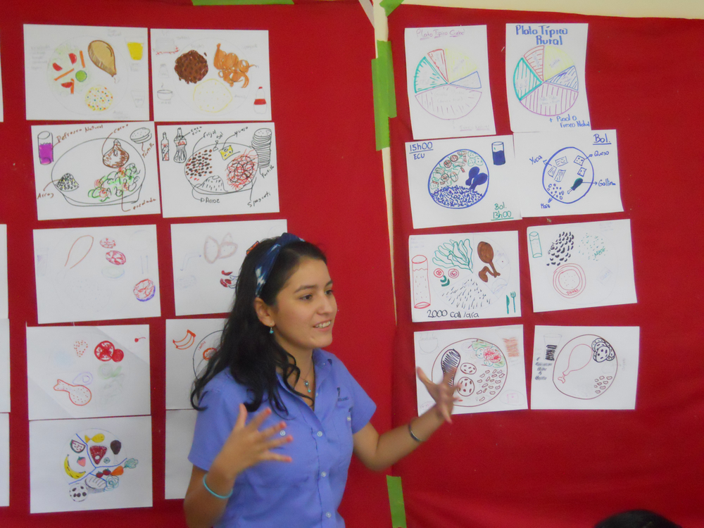 """A Zamorano student explains the difference between her diet (as a student) and that of a rural community during the """"What Goes on the Plate?"""" activity."""