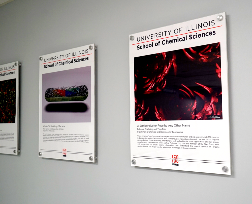 3 research artwork posters on a grey wall at Willard Airport