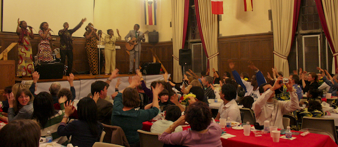 image of previous international dinner with crowd actively engaging in performance by five-person group