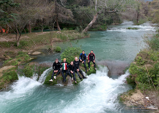 research team seated on a rock in the middle of rushing water in the Rio Valles, one of several collecting sites in San Luis Potosi