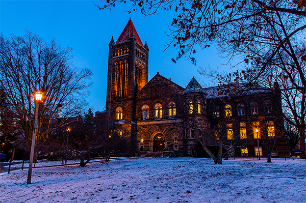 Altgeld Hall in winter with snow at dusk.