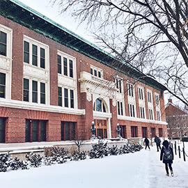 exterior of Lincoln Hall covered with snow and students walking to entrance