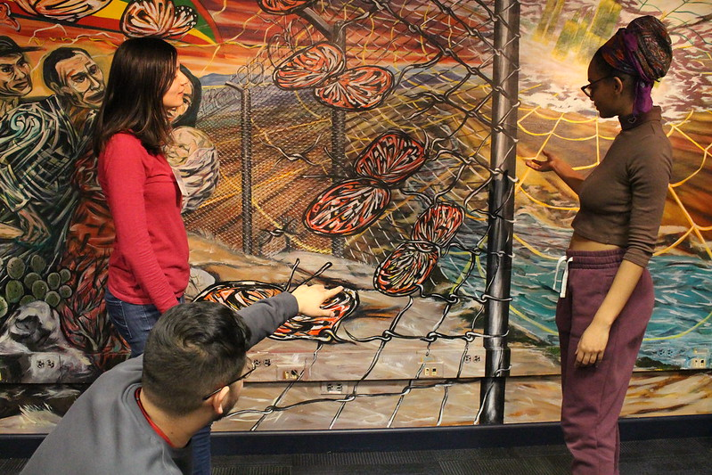 Students looking at a mural during 2019 Latinx Heritage Month celebrations.