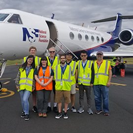 professor and students standing in front of an airplane