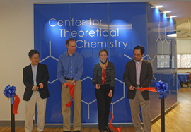 "4 people standing in front of a blue wall with ""Center for Theoretical Chemistry"" written on it, cutting an orange ribbon"