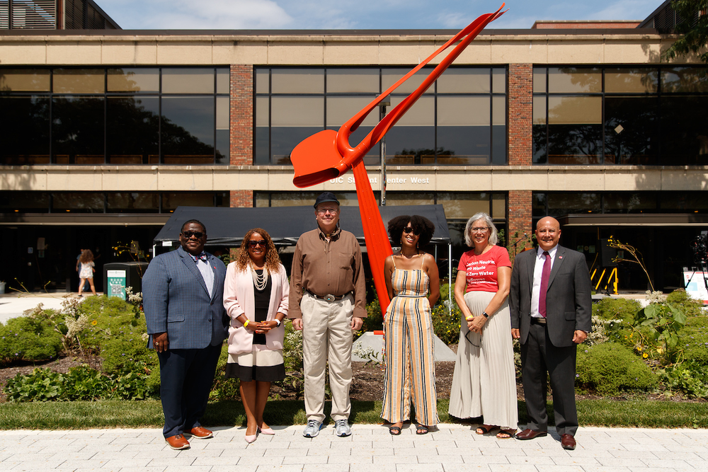 Six people standing in front of an orange sculpture on west side of UIC campus