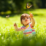 Child pointing up at butterfly in middle of green field