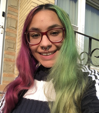 Smiling person with green and pink hair and dark eyeglasses