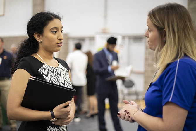 Neha Akella, left, a senior in biochemistry, spoke with a potential employer at the ACES + LAS Career Fair. (Photo by Jesse Wallace.)
