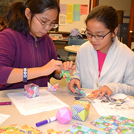 Sisters Jeana (left) and Grace To use mathematical principles to create origami shapes during an event hosted by the award-winning U of I chapter of the Association for Women in Mathematics. (Photo courtesy of AWM.)