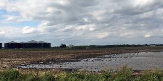Picture of a flat landscape with a muddy corn field, grain silos in the background.