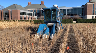 Combine harvester in corn field, university building in background.