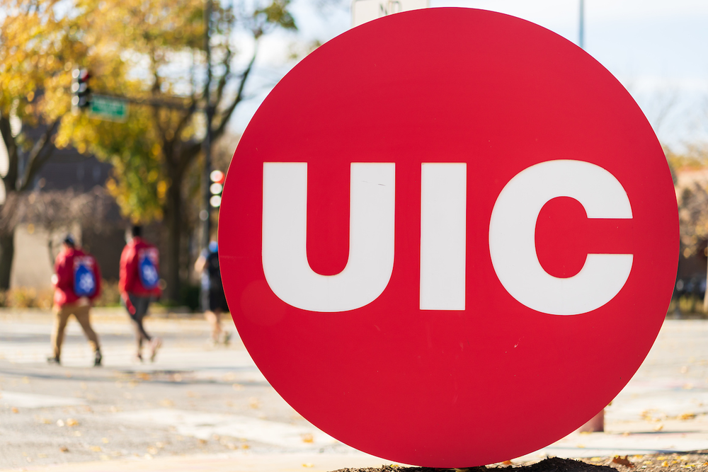 Close up of UIC red sign with people crossing the street in the background