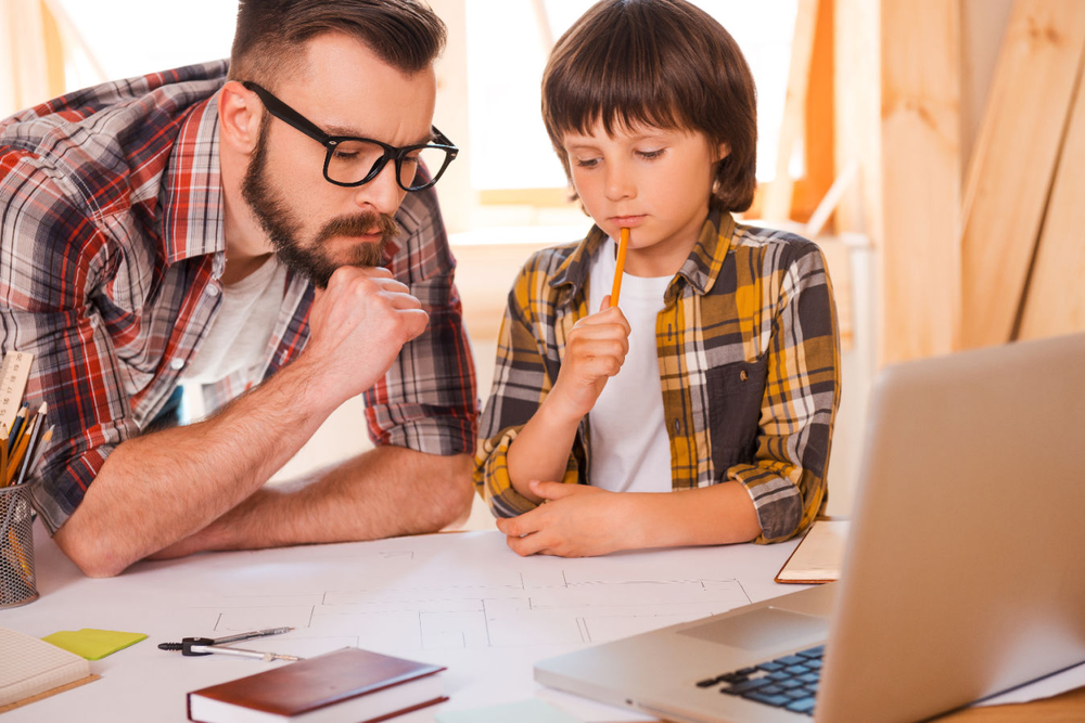 Father and son studying blueprints in front of laptop, working on a project together.