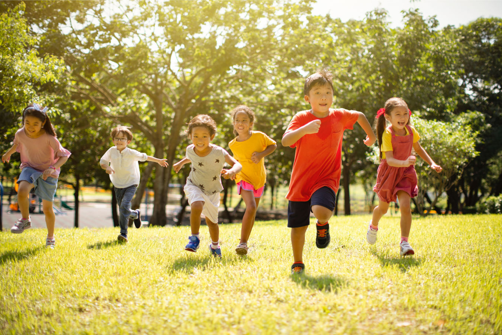 a group of children running outside in the sunshine