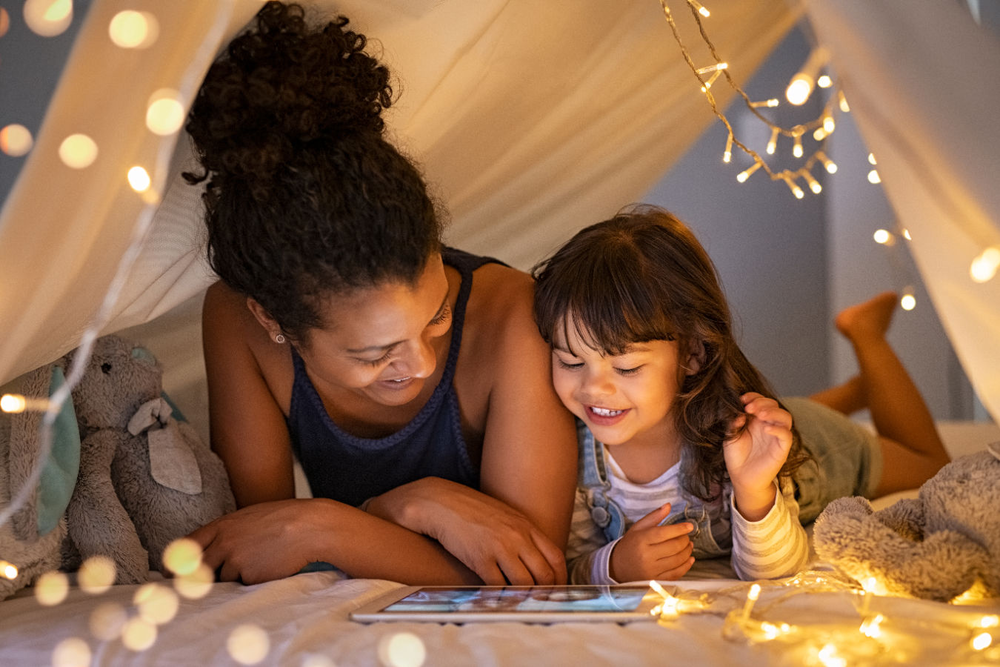 Woman and child reading a tablet in a white tent with festive party lights draped around them