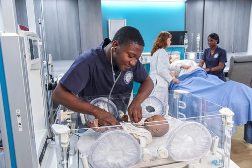 UIC College of Nursing students Saviour Karlo (front) and Sandra Ansong (back) with UIC instructor Karyn Roberts in the M. Christine Schwartz Experiential Learning and Simulation Laboratory. (Photo: Mark Mershon)