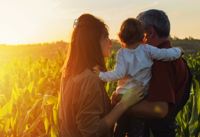 Man and woman holding child looking at field