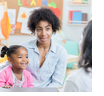 Mother with child sitting on lap listening to teacher