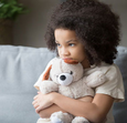 Young girl holding teddy bear