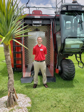 Ethan poses in front of a coffee harvester at the CNH Industrial Combine Factory