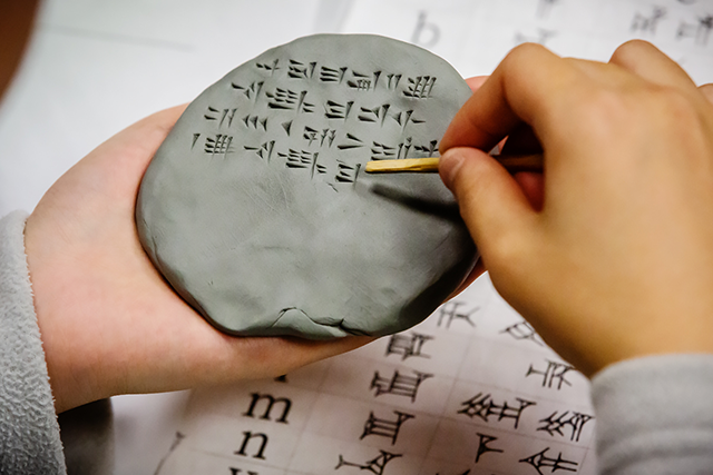 A student writes in Hittite using cuneiform symbols pressed into clay.