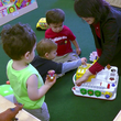 teacher and children playing with toy on the floor