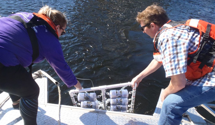 Maggie Oudsema, a research assistant at the Robert B. Annis Water Resources Institute (AWRI), Grand Valley State University and John Scott, a research chemist at ISTC, lower microplastic samples into Muskegon Lake. (Photo courtesy John Scott)