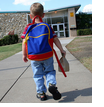 small boy walking up to school building