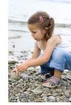 girl plays with rocks