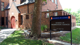 Photo of the exterior of the School of Information Sciences building with the sign for the building positioned prominently within the frame against the identifiable red brick building.