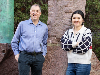 Photo of Prof. Andy Gewirth standing next to graduate student Stephanie Chen in a non-descript spot on campus