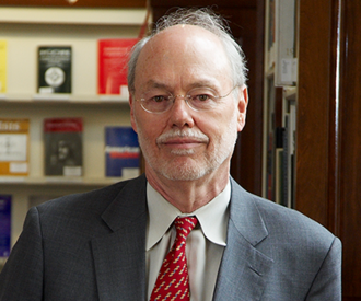 Head shot of Nobel Laureate Phillip Sharp in a suit jacket and tie with book shelves in the background