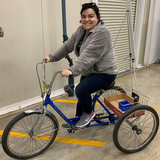 Tabitha Miller sitting on a large tricycle that's used as transportation at Argonne National Laboratory