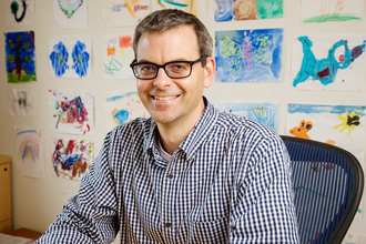 Portrait of Martin Burke in a blue shirt, sitting in an office with pictures on the wall behind him