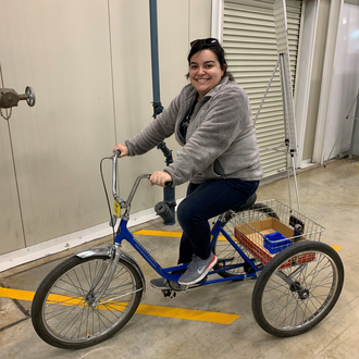 Tabitha Miller in a gray sweatshirt sitting on an adult-sized tricycle inside an Argonne National lab building