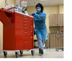 Health care worker in blue scrubs and gown pushing a red cart